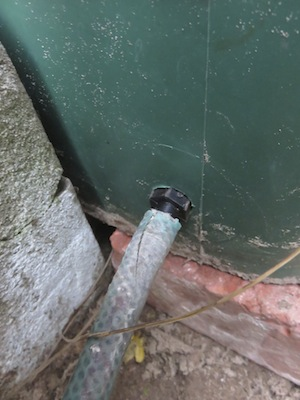 a flexible hose on a rain bin allows storage and easy targeted watering when needed