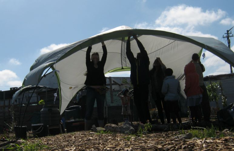 Assembling a domed tent for a township workshop.