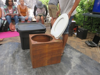 A wooden commode and a black plastic tote box which was turned into a toilet in about 15 minutes from scratch.